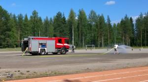 Palokunta kastelemassa urheilukenttää ennen pelien alkua.